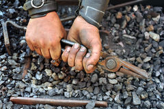 Detail of dirty hands holding pliers. Blacksmith Stock Images