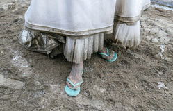 Detail of dirty white wedding dress and filthy foot covered by mud and dirt. Bride wearing thong sandals Stock Photography