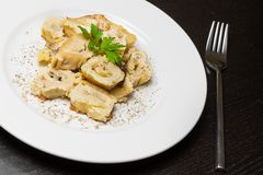 Detail of dish of italian swivels pasta with porcini mushrooms and sauce bechamel with pepper near fork stock image