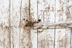 Detail of doorlock in wooden plank wall with peeling white color Royalty Free Stock Image