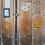 Detail of Doors, Rusted Shipping Container. Rusted doors of an old shipping container, with load weight limits and volume capacity stencils and a super heavy Royalty Free Stock Photography