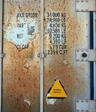 Detail of Doors, Rusted Shipping Container. Rusted doors of an old shipping container, with load weight limits and volume capacity stencils and a super heavy Stock Photos
