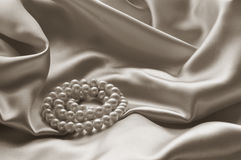Detail of draped beige silk fabric with pearl Stock Images