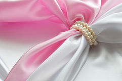 Detail of draped white and pink silk fabric with pearl Stock Photo