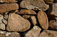 Detail of a dry stone wall on the island of Lindisfarne. Detail of an interesting stone, possibly from the local Priory, used in the construction of a dry stone Royalty Free Stock Photo