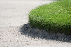 Detail of edge of golf sand bunker. Edge of carefully maintained lawn ends in bunker Stock Images