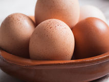 Detail of eggs inside a clay plate over wooden background Royalty Free Stock Images