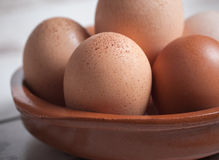 Detail of eggs inside a clay plate over wooden background. In a studio shot Royalty Free Stock Photography