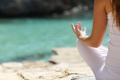 Detail einer Frauenhand, die Yoga tut, trainiert auf dem Strand Stockfotografie