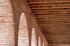 Detail einer gewölbten Ziegelsteinstruktur mit herausgestellten Holzbalkendachsparren stockbild