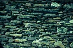 Detail einer Wand eines alten Steinhauses Grün getont Stockfotografie