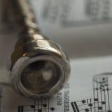 Detail eines alten silbernen Trompetenmundstücks auf Notenenmusikbuch Lizenzfreie Stockfotos