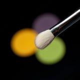 Detail eines Augenschminkepinsels über 3 Augenschminken Stockfotos
