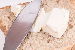 Detail eines ausgebreiteten Käses des Messers auf einer Brotscheibe auf weißem BAC Stockbild