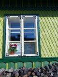 Detail eines Fensters eines gemeißelten und verzierten grünen hölzernen Hauses von Rumänien mit etwas Brennholz in der Extremität Lizenzfreies Stockfoto