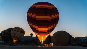 Detail eines großen Heißluftballons, der mit Feuer an der Dämmerung aufgeblasen wird Lizenzfreies Stockfoto