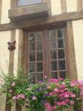 Detail eines hölzernen Fensters von Britany in Frankreich mit Blumen vor und hölzerner Hauptstatue von Frauen stockbild