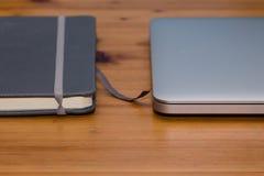 Detail eines Notizbuches und des Laptops auf Holztisch Stockfotografie