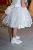 Detail eines weißen Kleidermädchens mit einem Bogen und weißen Herzen, der weißen Socken und der Schuhe auf seinen Füßen Stockfotos