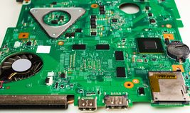 Detail of an electronic printed circuit board with many electrical component. Close up side view image of microchips. Green microchips of motherboard for stock photography