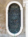 Ornate Bronze Window Grill, Venice, Italy. Detail of an elongated window on an aged stucco or rendered building, with a heavily patinated ornate bronze grill and Stock Images