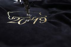 Detail of embroidery machine stitching 2019 chinese new year motive with precious gold yarn on black velvet. Tilted view with blurred surrounding as copy royalty free stock images