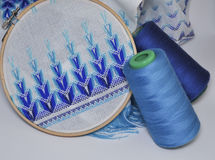 Detail of embroidery products with blue thread in wooden hoop Royalty Free Stock Photography