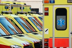 Detail of emergency ambulance cars in hospital yard. Detail of yellow emergency ambulance cars in hospital yard Stock Images