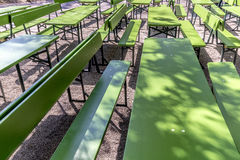 Detail of empty beergarden tables in the english Garden. In Munich in spring Royalty Free Stock Photo