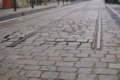 Detail of an end of rail tracks among cobbled road as a symbol of terminal station. Detail of an end of rail tracks among cobbled road as symbol of terminal Royalty Free Stock Images