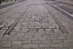 Detail of an end of rail tracks among cobbled road as a symbol of terminal station. Detail of an end of metal rail tracks among cobbled road as a symbol of Stock Images