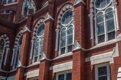 Detail exterior architecture of red brick Gothic Revival church with arched windows. Horizontal aspect royalty free stock image