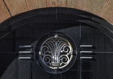 Detail of exterior Art Deco architectural style terracotta building with doorway arch and metal emblem on black grainite. Detail of exterior Art Deco Royalty Free Stock Photo