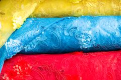 Detail of fabric rolls stacked in yellow, blue and red colors for sale at a fabric store royalty free stock image