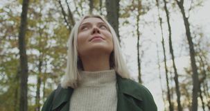 Detail on face. Caucasian blond woman slomo looking around fall woods. Static. Storytelling real young adult people alone stock video
