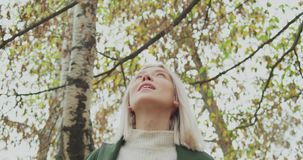 Detail on face. Caucasian blond woman slomo walking through fall woods.Following in front gimbal.Storytelling real young stock video
