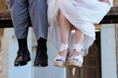 Detail of the feet of the groom and the bride sitting on a scaff Stock Images
