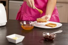 Woman spreading honey over toasted bread slice. Detail of female hands holding toasted bread slice and wooden spoon, spreading honey over the bread; woman making royalty free stock photography