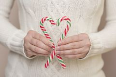 Candy cane heart. Detail of female hands holding two candy canes forming heart shape. Focus on the top of the candy cane stock photography