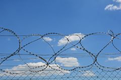 Barbed wire detail. Detail of a fence with sharp edges against blue sky with clouds royalty free stock image