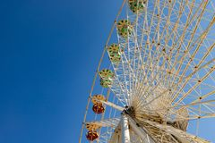 Detail of a Ferris wheel and its gondolas on a fairground in fro. Nt of a blue sky stock image