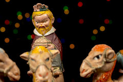 Detail of figurine of King Melchior. Nativity scene. Christmas traditions. Detail of Melchior riding his camel, with colorful stars at background. Nativity Royalty Free Stock Photo