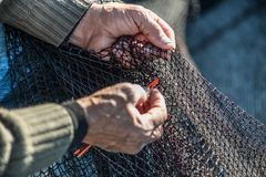 Detail fisherman mending. Old fisherman mending the nets Royalty Free Stock Photography