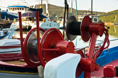 Detail of a fishing boat in a harbor with red colorful machinery Stock Photo