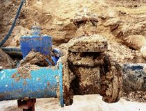 Detail of fittings, 250mm and 150mm gate valves, reduction joint members in drink water system. Repairing of piping in excavation pit. Extreme kind of Stock Photos
