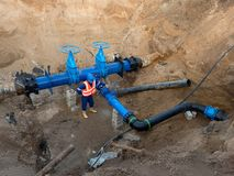 Detail of fittings, 250mm and 150mm gate valves, reduction joint members in drink water system. Repairing of piping in excavation pit. Extreme kind of Royalty Free Stock Photo