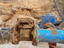 Detail of fittings, 250mm and 150mm gate valves, reduction joint members in drink water system. Repairing of piping in excavation pit. Extreme kind of Royalty Free Stock Photos