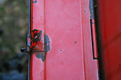 DETAIL OF FLAP ON SIDEBOX LATCH. Flap of latch on sidebox of old red tractor Royalty Free Stock Photo