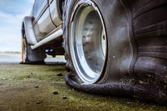 Detail of a flat black offroad tire on a offroad truck vehicle. Damaged flat offroad tire on a road royalty free stock photo