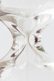 Detail of flowing white sand crystal in hourglass on white backg. Round, time concept Stock Photography